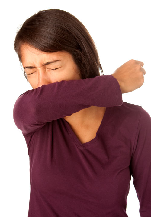Image of a Woman sneezing into her elbow