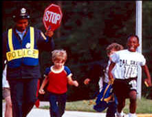 photograph of a crossing guard stopping traffic and children crossing the street